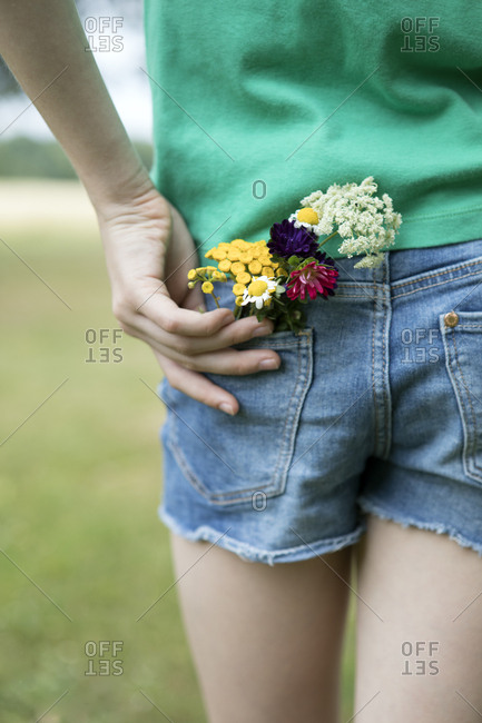 Flowers in pocket of girl's jeans shorts