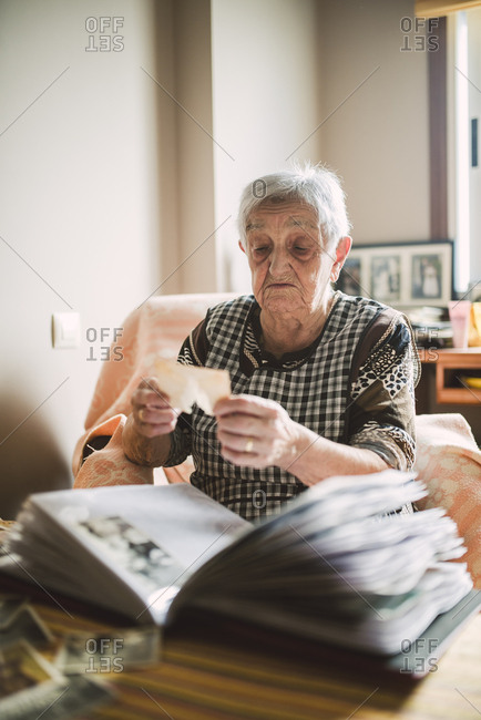 Senior woman looking at photo before adding it into a photo album