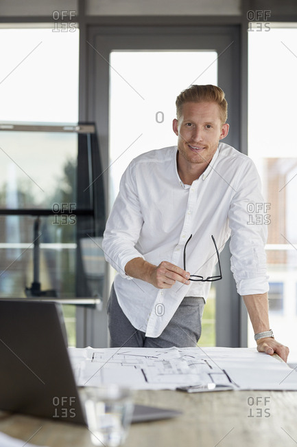Portrait of smiling young man working on blueprint on desk in office