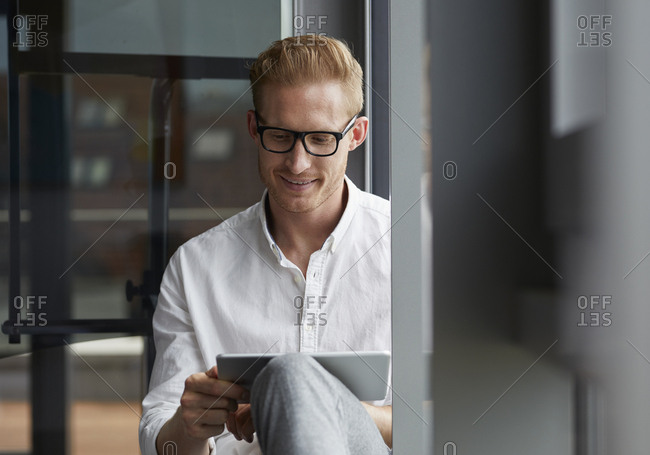 Smiling businessman sitting on windowsill using tablet