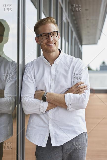 Portrait of smiling businessman leaning against window
