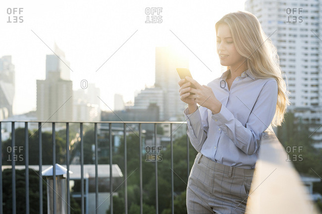 Blonde business woman checking smartphone on city rooftop