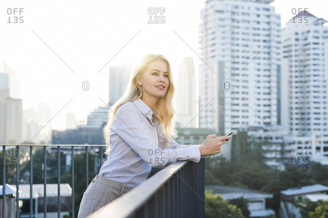Blonde smiling business woman leaning onto handrail holding smartphone on city rooftop