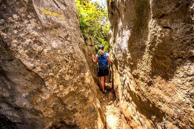 Spain- Malaga Province- El Torcal- woman hiking through gorge