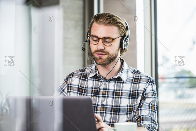 Businessman with headset in office using laptop