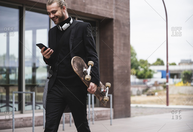 Smiling fashionable young man holding cell phone and skateboard passing office building