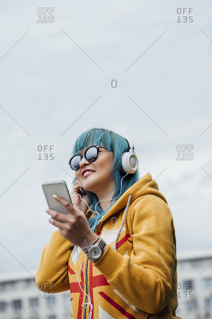 Portrait of young woman with dyed blue hair listening music with smartphone and headphones