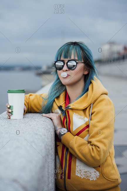 Portrait of young woman with dyed blue hair wearing mirrored sunglasses and fashionable hooded jacket