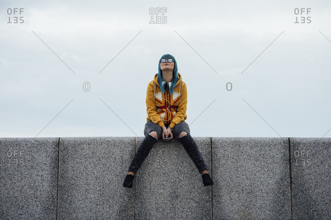 Young woman with dyed blue hair sitting on a wall looking up