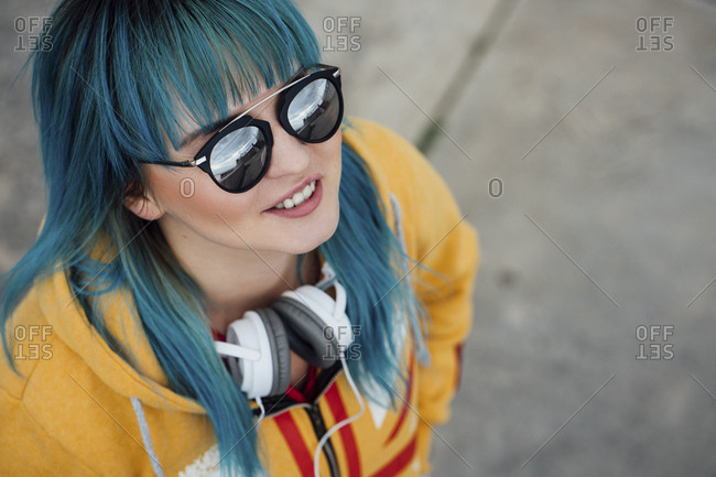 Portrait of young woman with dyed blue hair and headphones looking up