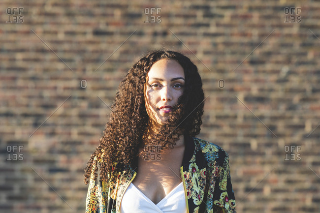 Portrait of young woman with curly hair in front of brick wall