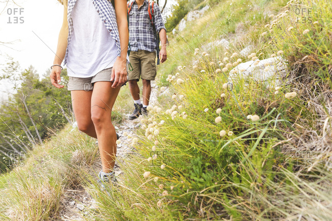 Italy- Massa- legs of young couple hiking in the Alpi Apuane mountains