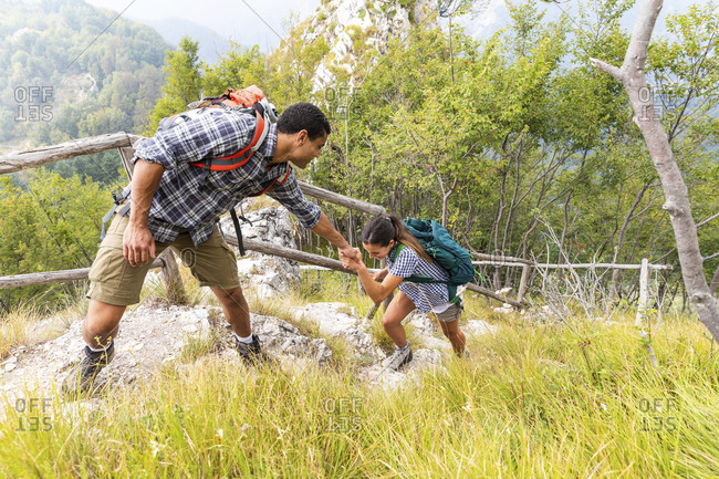 Italy- Massa- man helping a young woman to climb a step while hiking in the Alpi Apuane mountains