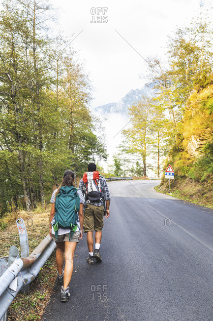 Italy- Massa- rear view of young couple walking on asphalt road in the Alpi Apuane mountains