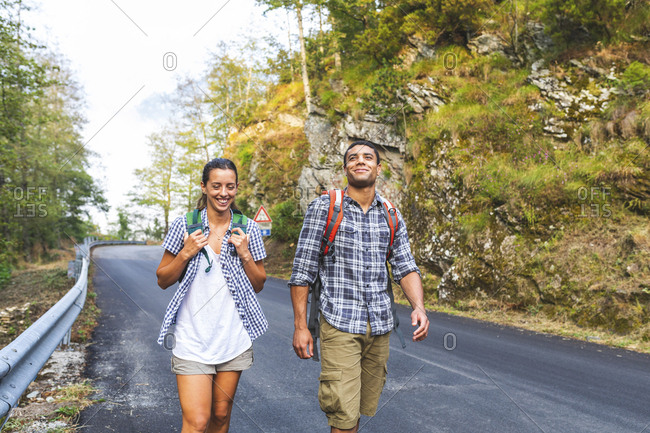 Italy- Massa- smiling young couple walking on asphalt road in the Alpi Apuane mountains