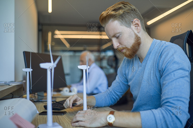 Man in office with model wind turbines