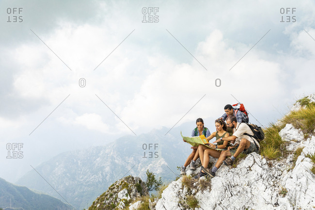 July 29, 2018: Italy- Massa- group of people hiking and looking at a map in the Alpi Apuane