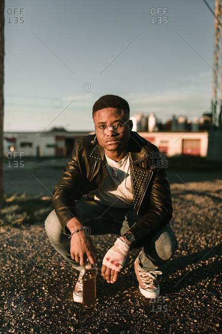 African american boy crouched down with wounds holding a beer in a sunset