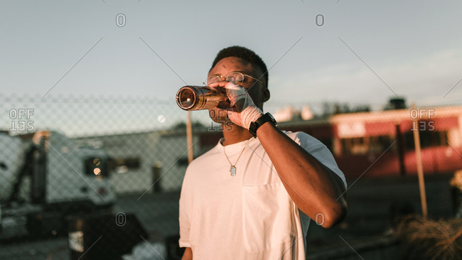 Side view of african american guy with bandage on his hand drinking beer in a sunset