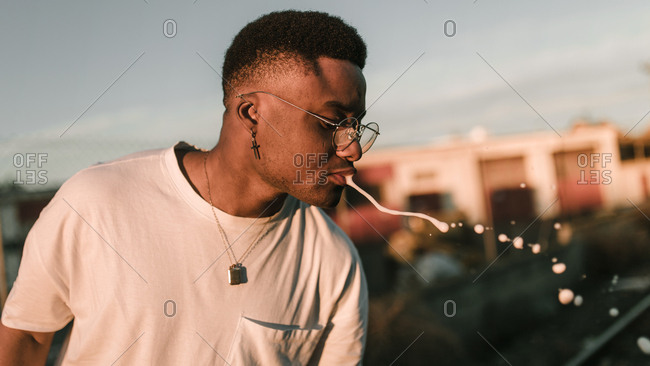 Side view of african american guy spitting beer