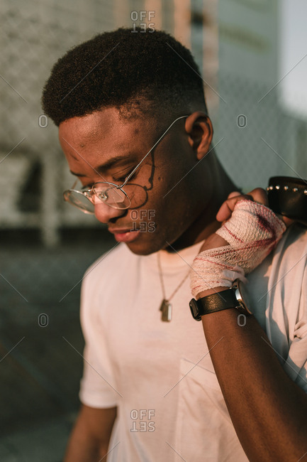 Side view of young african american boy with broken glasses in a sunset