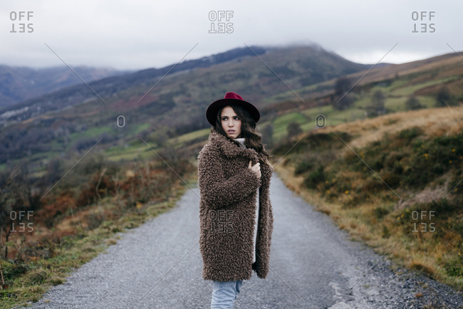 Attractive caucasian woman with hat and coat standing on the county road