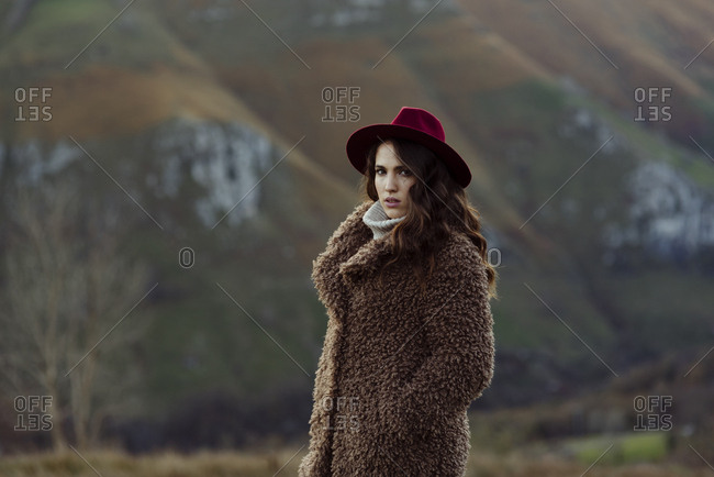 Attractive caucasian woman with coat and hat standing in the mountains on a winter day