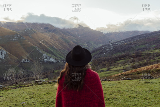 Unrecognizable woman dressed with a red blanket and hat looking at the mountains on a winter day
