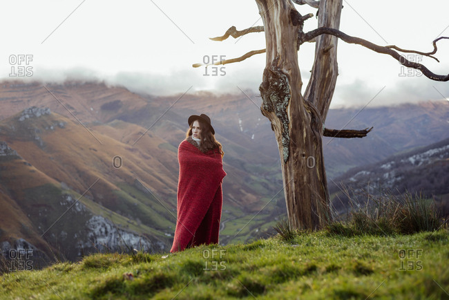 Attractive caucasian woman with a red blanket and hat standing in the mountains on a winter day