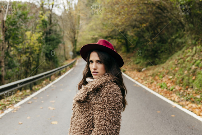 Attractive brunette woman portrait dressed with coat and hat in the middle of the road on autumn day