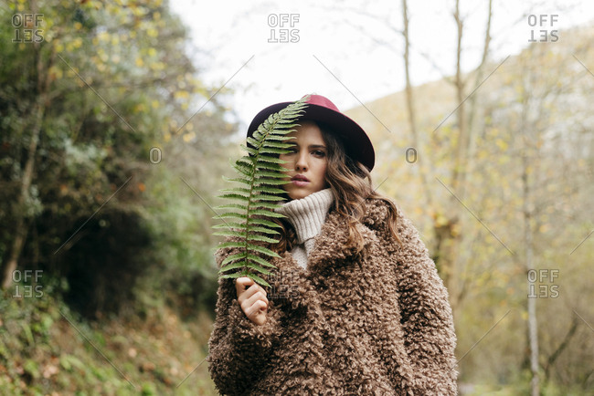 Attractive trendy caucasian girl with hat hiding her face with a fern leaf in the forest on an autumn day