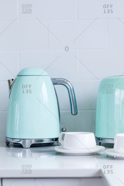 Blue tea kettle and toaster by sink