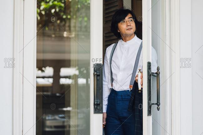 Elegant Asian man opening the hotel doors.