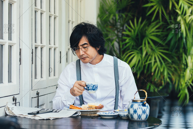 Serious middle-aged Asian businessman having a breakfast at hotel terrace and reading newspaper while drinking a tea.