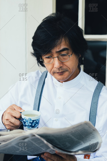 Serious Asian man with suspenders reading a newspapers and drinking tea.