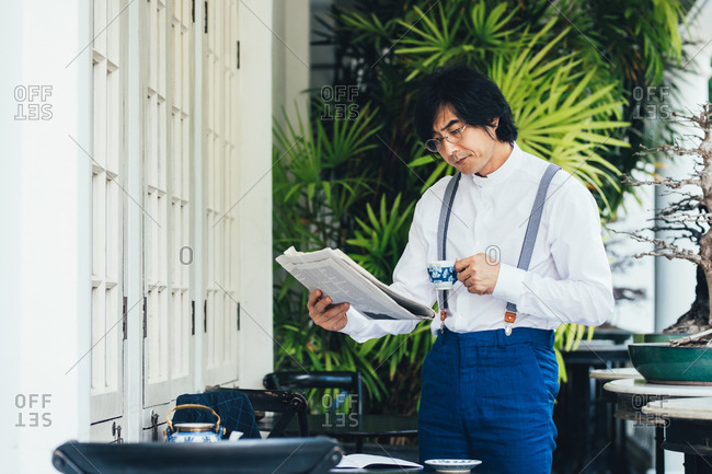 Elegant Asian man with suspenders standing on terrace and reading newspapers in the morning.