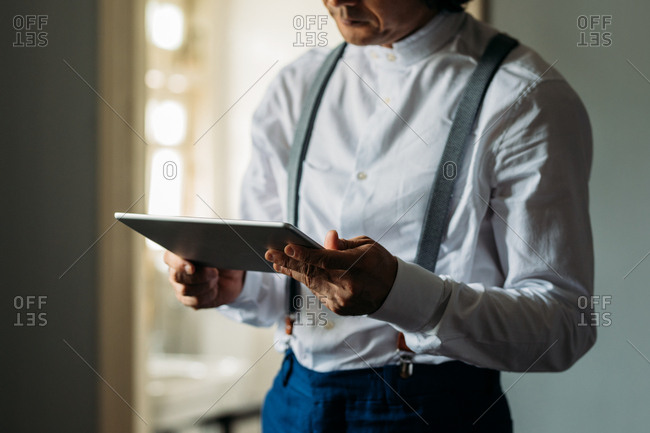 Unrecognisable elegant man with suspenders holding a tablet.