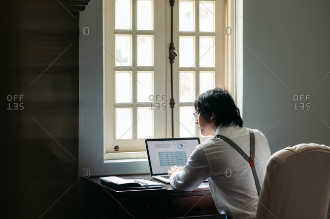 Back view of businessman with suspenders working on a laptop.