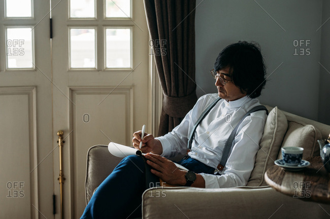 Serious middle-aged Asian businessman sitting at cozy armchair and writing in his notebook.