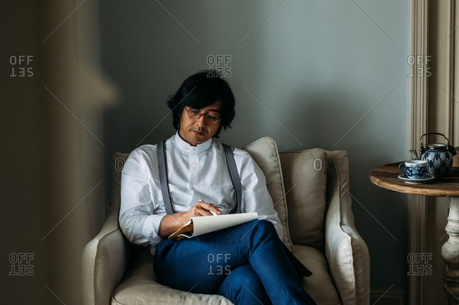 Serious middle-aged Asian man sitting at cozy armchair and writing in his notebook.