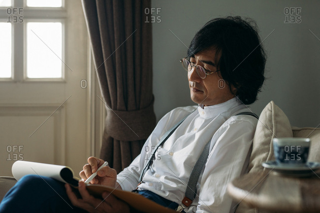 Portrait of elegant Asian man wearing glasses and suspenders and writing.