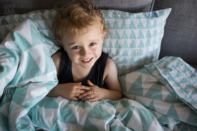 Toddler boy tucked in with blankets and pillows on sofa