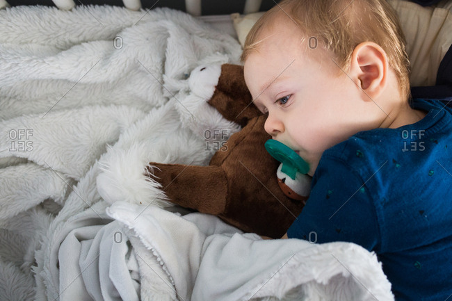 Baby sleeping on top of soft stuffed animal