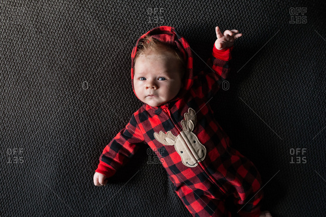 Baby wearing red plaid moose pajamas
