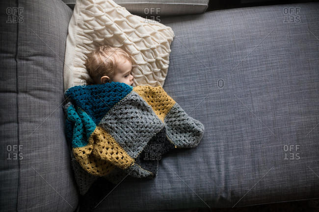 Overhead view of baby snuggled on sofa with crocheted blanket and pillow