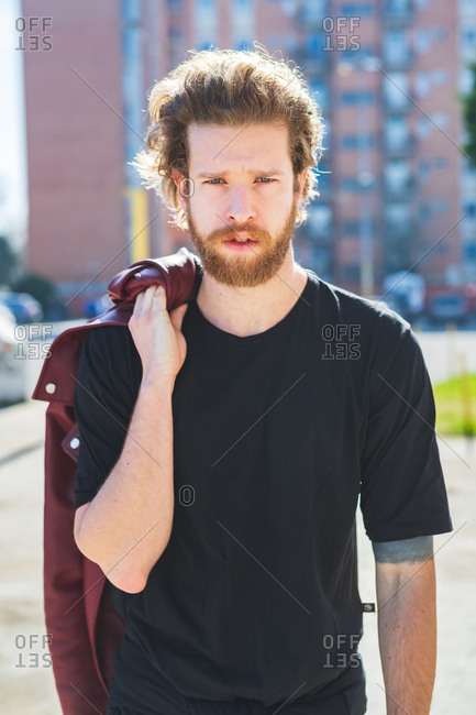 Young bearded man posing outdoor looking camera close up