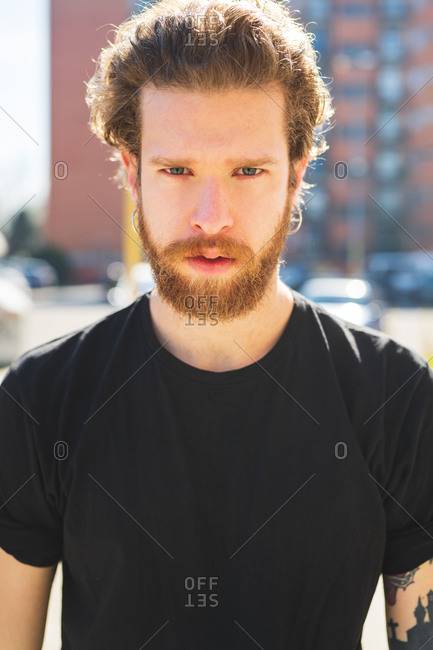 Close up of a young bearded man posing outdoor looking camera close up