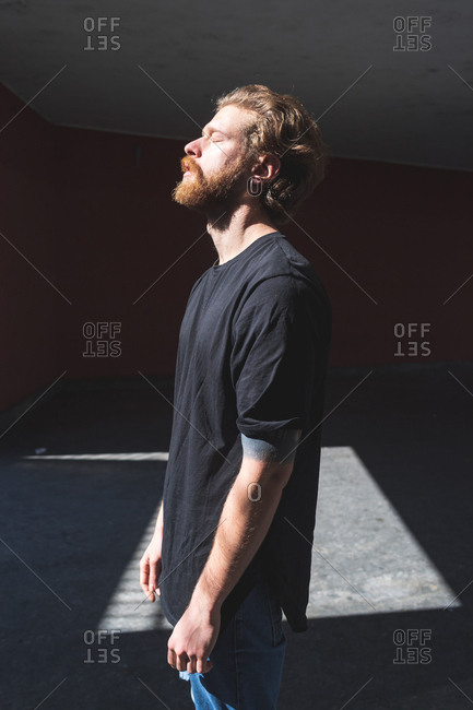 Young bearded man posing outdoor looking away