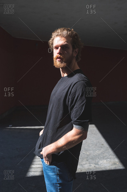 Bearded young man posing outdoor looking away