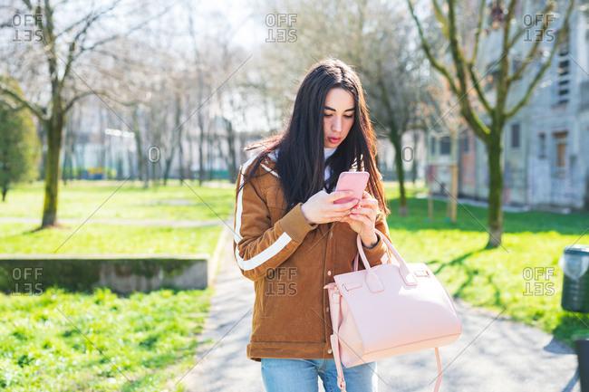 Young beautiful woman outdoor using smart phone